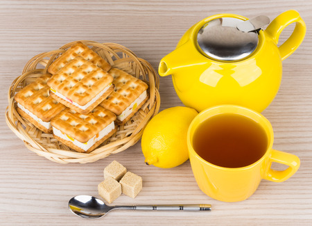 tea and biscuits: Cup of tea, biscuits, lemon and lumpy sugar on table