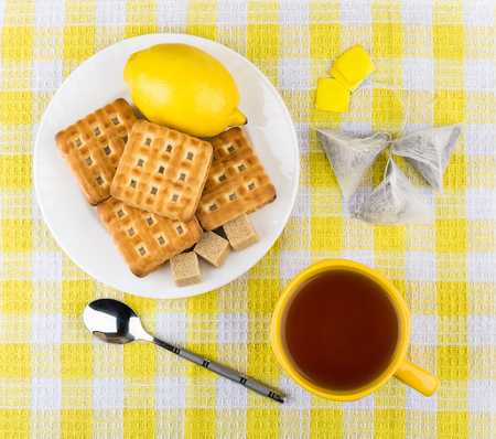 tea and biscuits: Cup of tea, biscuits and lemon in plate on table, top view Stock Photo
