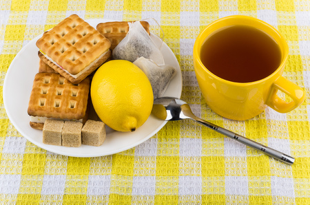 tea and biscuits: Cup of tea, biscuits and lemon in plate on table Stock Photo