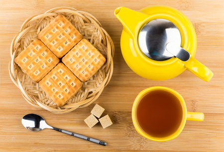 tea and biscuits: Cup of tea, biscuits and sugar cubes on wooden table, top view Stock Photo