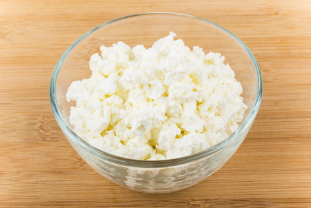 casein: Heap of cottage cheese in transparent glass bowl on wooden table