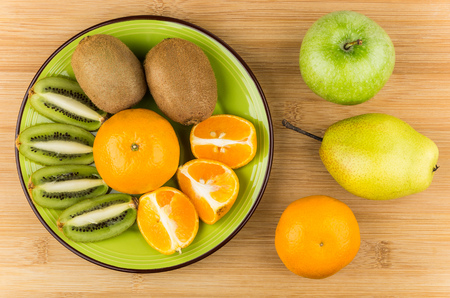 hairy pear: Slices of various fruits in green plate on wooden table