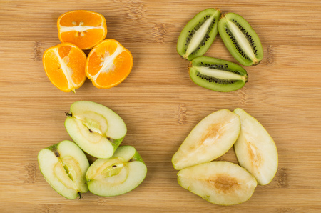 hairy pear: Slices of various fruits on bamboo wooden board Stock Photo