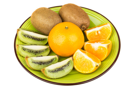 isolated on green: Slices of various fruits in green plate isolated on white background Stock Photo