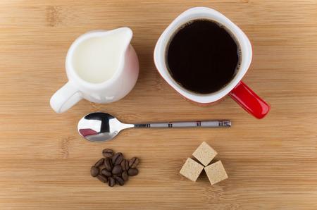 azucar: Taza roja con caf�, cuchara, granos de caf� y jarro de leche en la mesa de madera. Vista superior Foto de archivo