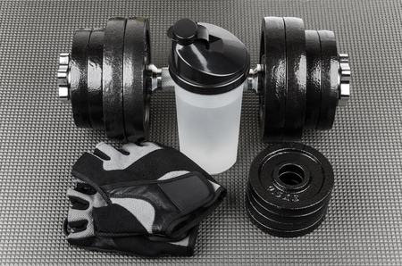 weightlifting gloves: Ajustable dumbbells, training gloves and shaker on grey mat