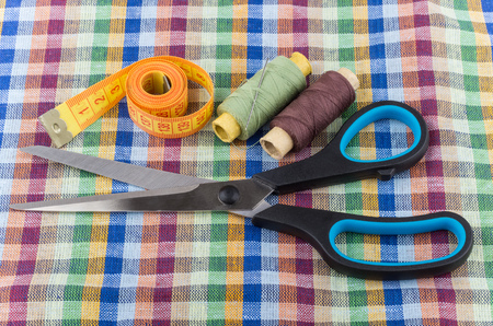 sartorial: Sartorial scissors, tape-line, threads and needles on checkered fabric Stock Photo