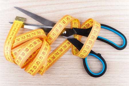 cintas metricas: tijeras de sastre y l�nea de la cinta sobre la mesa de madera. Vista superior