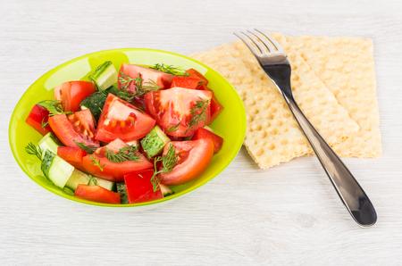 salad fork: Vegetable salad, fork and crispbread on wooden table