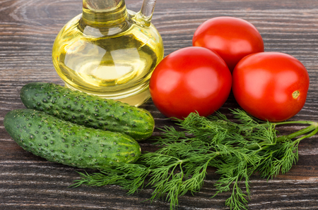 sunflower oil: Bottle of sunflower oil, tomatoes, cucumbers and dill on wooden table Stock Photo