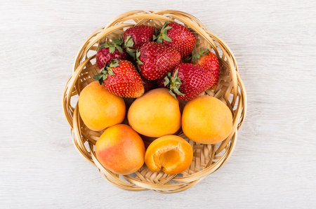 fruits in a basket: Wicker basket with apricots and strawberries on wooden table. Top view