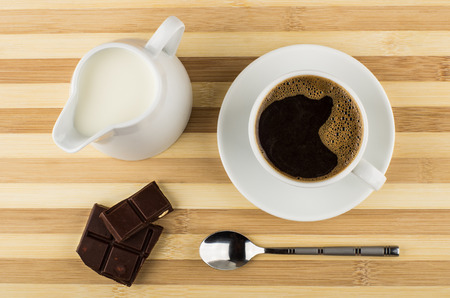 Black coffee, chocolate and jug of milk on striped table. Top view
