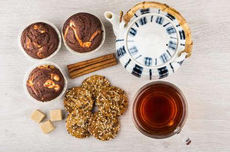 Tea, teapot, cookies, cupcakes and cinnamon sticks on table. Top view Stock Photo