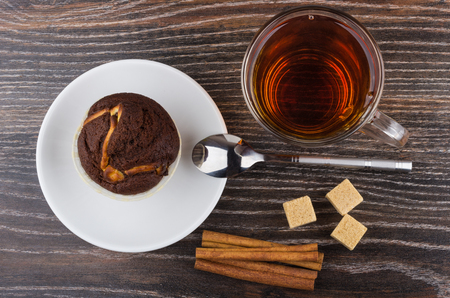 Cupcake in saucer, cinnamon sticks, sugar and tea on wooden table. Top view