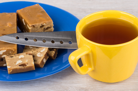 sherbet: Pieces of sherbet with peanut and raisins, knife, tea on wooden table