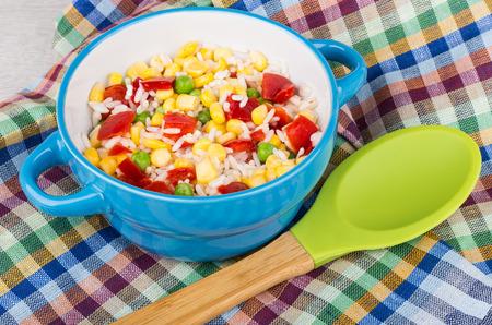 silicio: tazón de vidrio azul con la mezcla de verduras en la servilleta a cuadros y una cuchara de silicio