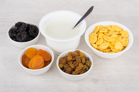 frutos secos: Jar of yogurt and dried fruits, corn flakes in bowls on wooden table