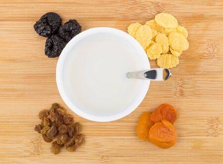 frutos secos: Tarro de yogur, fruta seca montón y de copos de maíz en la mesa de bambú. Vista superior