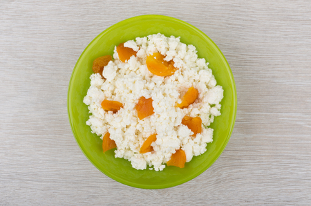 Cottage cheese with pieces dried apricots in green bowl on wooden table. Top view Stock Photo