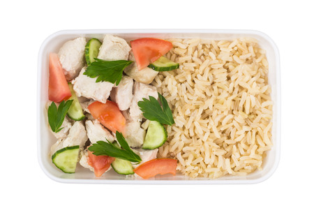 Chicken with brown rice and vegetables in plastic container isolated on white background. Top view