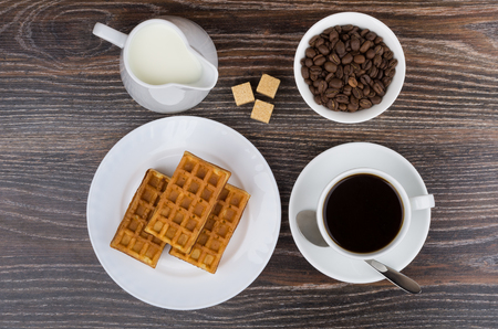 viennese: Cup, jug milk, bowl with coffee beans and viennese waffles on wooden table. Top view