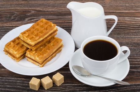 Black coffee with viennese waffles, sugar and jug milk on wooden table