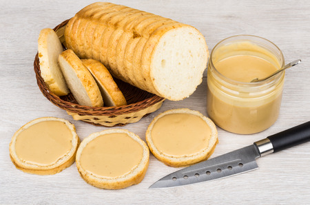 Sandwiches with peanut butter, plastic jar, bread and knife on table Stock Photo