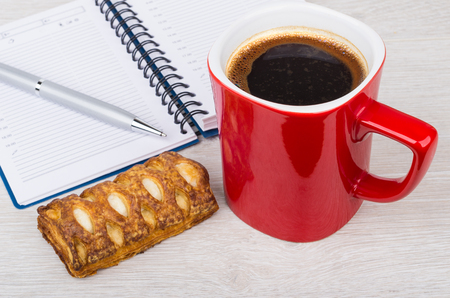 yellow notepad: Red coffee cup, cookie, notepad and ball point pen on wooden table Stock Photo