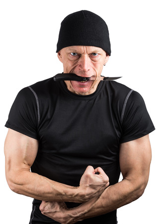 Angry man with knife in his mouth and with his fists isolated on white background