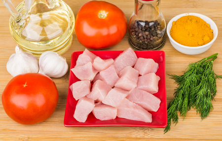 vegetable oil: Pieces of chicken meat in red plate, tomatoes, spices, garlic and vegetable oil on bamboo table Stock Photo
