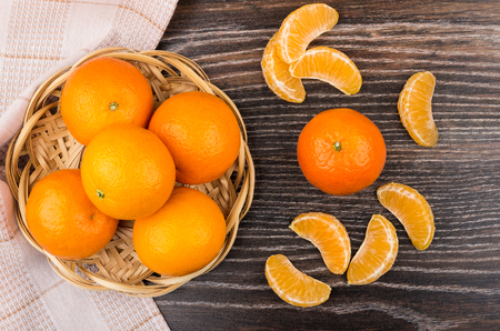 fruits in a basket: Wicker basket with tangerines and slices of tangerines on dark table. Top view Stock Photo