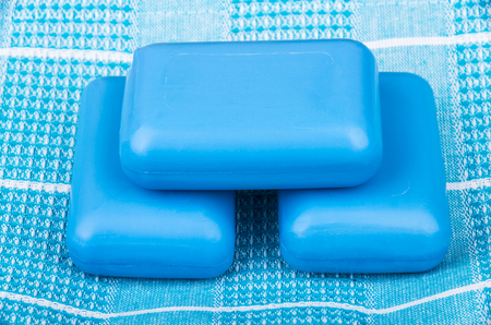 roundish: Three pieces of blue soap on checkered towel