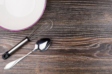 Whisk, spoon and ceramic bowl on dark table from left side. Top view