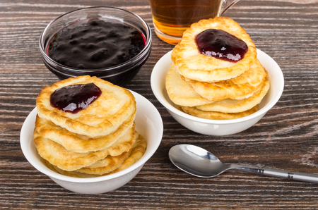 teaspoon: Bowls with stack of pancakes with jam, teaspoon and tea on wooden table