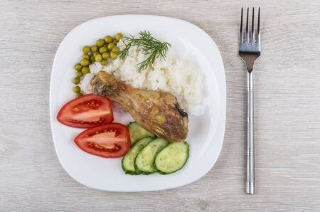 rice plate: Fried legs with vegetable and rice in glass plate on wooden table. Top view