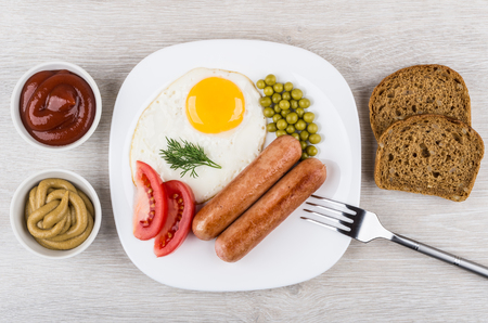 scrambled: Fried egg and sausages in glass plate, ketchup, mustard and pieces of bread. Top view