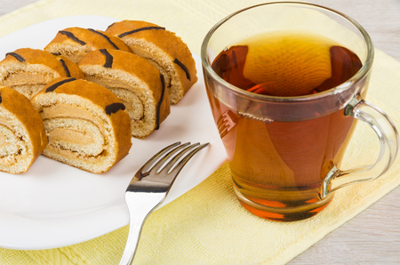 Pieces of swiss roll cake in dish on yellow towel, fork and tea on wooden table