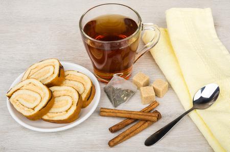 Swiss roll cake, sugar, tea bag, teacup and cinnamon sticks on wooden table
