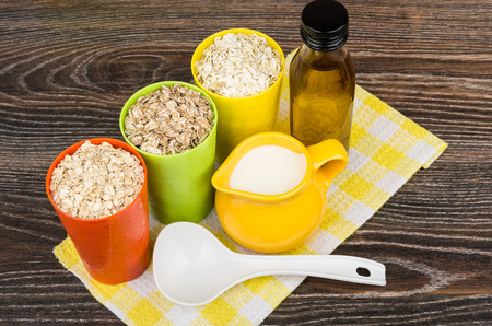 vegetable oil: Bowl and cups with oat, rye, barley flakes, vegetable oil and jug milk on yellow napkin