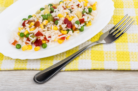 Vegetable mix in white dish and fork on yellow napkin. Top view Stock Photo