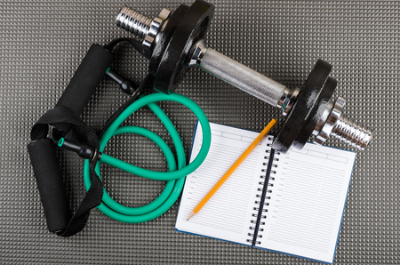 Rubber tubular expander, adjustable dumbbell, notepad and pencil on grey mat. Top view