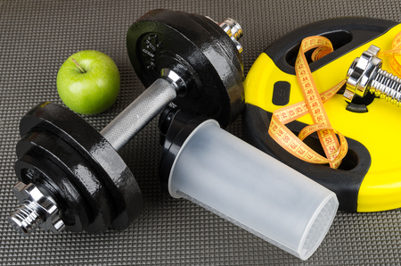 Adjustable dumbbells, weight, plastic shaker, apple and measures tape on mat