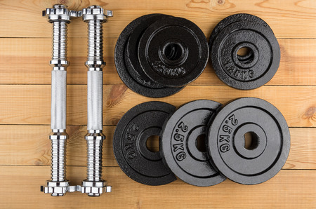 adjustable dumbbell: Disassembled dumbbells on wooden table. Top view