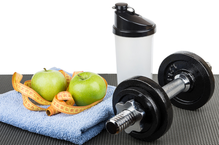 Two green apples, measures tape on blue towel, plastic shaker and dumbbell on mat isolated on white background Stock Photo
