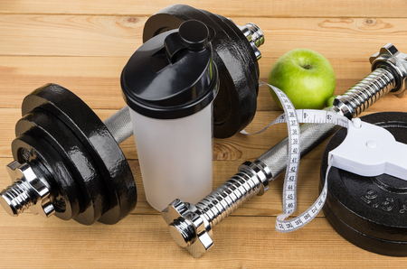 adjustable dumbbell: Adjustable dumbbells, plastic shaker, apple and measures tape on wooden table Stock Photo