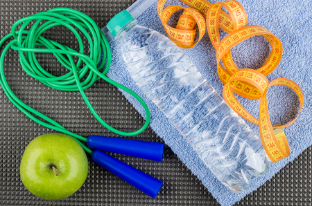 saltar la cuerda: Measures tape and bottle of water on towel, jump rope and apple on grey mat. Top view