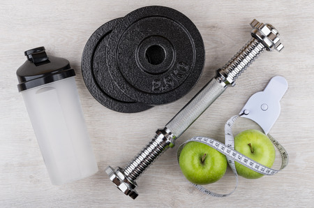 Disassembled dumbbell, plastic shaker, green apples and measures tape on wooden table. Top view Stock Photo