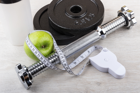 adjustable dumbbell: Disassembled dumbbell, green apple and measures tape on wooden table