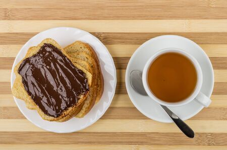 smeared: Sandwich with chocolate cheese, pieces of bread in plate and tea on striped table. Top view