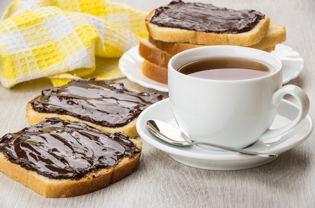 Sandwiches with chocolate cheese, cup of tea and teaspoon on table